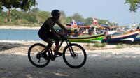 Peserta memacu sepeda ketika mengikuti Rhino Cross Triathlon 2018 di Kawasan KEK Tanjung Lesung, Pandeglang, Banten, Minggu (30/9). Rhino Cross Triathlon diikuti lebih dari 200 peserta dari dalam negeri dan manca negara. (Liputan6.com/HO/Nick Hanoatubun)