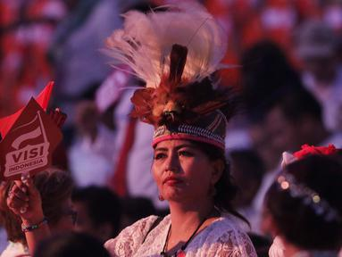 Salah satu relawan pendukung bersiap menyaksikan pidato Visi Indonesia yang akan disampaikan Presiden/Wakil Presiden terpilih 2019-2024, Joko Widodo dan KH Ma'ruf Amin di SICC, Kab Bogor, Jawa Barat, Minggu (14/7/2019). (Liputan6.com/Helmi Fithriansyah)