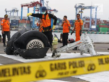 Petugas menyemprot cairan pada bagian roda pesawat Lion Air PK-LQP JT 610 di Pelabuhan JICT 2, Jakarta, Senin (5/11). Bagian tersebut dipindah untuk dilakukan identifikasi dan pengecekan lebih lanjut oleh KNKT. (Liputan6.com/Helmi Fithriansyah)