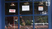 Seorang pria berada di balik kaca sebuah kedai kopi yang tutup di kawasan Sabang, Jakarta, Sabtu (3/7/2021). Rumah makan hingga restoran diizinkan buka hanya untuk melayani layanan delivery order atau takeaway selama PPKM Darurat. (Liputan6.com/Angga Yuniar)