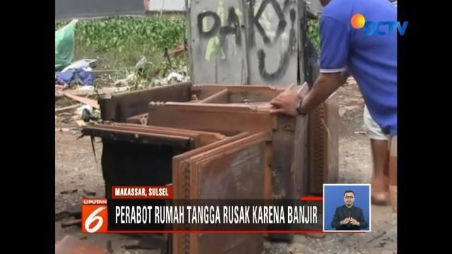Warga Kampung Beru Antang, Sulawesi Selatan, mulai membersihkan sisa banjir di rumah.