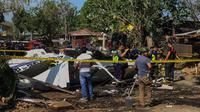 Penyelidik berdiri di dekat puing-puing Helikopter bell 429 yang membawa kepala polisi Filipina setelah jatuh di Kota San Pedro, selatan Manila, Kamis (5/3/2020). Tidak ada yang tewas dalam kejadian tersebut, dan semua penumpang dibawa ke rumah sakit untuk menjalani perawatan. (AFP)