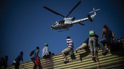 Sebuah helikopter terlihat saat para imigran memanjat pagar perbatasan antara Meksiko dan AS di Tijuana, Meksiko (25/11). Ratusan migran berusaha menyerbu pagar perbatasan yang memisahkan Meksiko dari AS. (AFP Photo/Pedro Pardo)