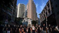 Para siswa, alumni dan guru membentuk rantai manusia di area Mid-Levels, Hong Kong, Senin (9/9/2019). Aksi dilakukan para siswa yang masih berseragam sekolah sambil memakai masker sebagai bentuk dukungan terhadap demonstran anti pemerintah setelah bentrokan pada akhir pekan. (Anthony WALLACE/AFP)