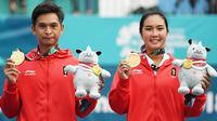 Petenis ganda campuran Indonesia Christopher Rungkat (kiri) dan Aldila Sutjiadi menggigit medali emas pada upacara penganugerahan medali seusai menang atas petenis Thailand Luksika Kumkhum dan Sonchat Ratiwatana pada final tenis ganda campuran Asian Games