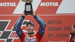 Pebalap Ducati, Andrea Dovizioso, mengangkat trofi usai mejuarai balapan MotoGP Jepang di Sirkuit Motegi, Minggu (15/10/2017). Andrea Dovizoso menyelesaikan balapan dengan catatan waktu 47 menit 14,236 detik. (AP/Shizuo Kambayashi)