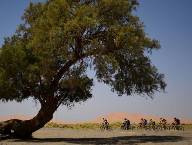 Para pebalap mengendarai sepeda pada etape 1 edisi ke 14 balap sepeda gunung Titan Gurun 2019 di sekitar Kota Merzouga, Maroko, Minggu (28/4/2019). Trek Titan Gurun 2019 sepanjang 640 km menghubungkan antara Merzouga dan Maadid berlangsung pada 28 April-3 Mei 2019. (Franck Fife / AFP)