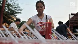 Seorang wanita menyiapkan hidangan berbuka puasa di Vihara Dharma Bhakti, Glodok, Jakarta, Rabu (30/5). Acara yang pertama kali digelar pada Ramadan tahun ini sebagai kegiatan untuk menjalin keharmonisan antar-umat beragama. (Merdeka.com/Iqbal S. Nugroho)