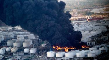 Gumpalan asap membubung dari kebakaran tempat penyimpanan bahan petrokimia di Intercontinental Terminals Co (ITC) di Deer Park, Texas, Senin (18/3). Diperkirakan, kebakaran ini akan terus membakar hingga dua hari ke depan. (AP/David J. Phillip)
