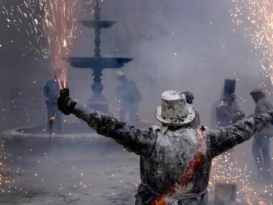Peserta memegang petasan saat mengikuti festival Els Enfarinats di kota Ibi dekat Alicante, Spanyol (28/12). Selama sekitar 200 tahun penduduk Ibi setiap tahun merayakan dengan pertempuran menggunakan tepung, telur, dan petasan. (AP Photo/Alberto Saiz)