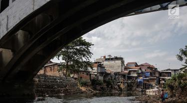 Warga beraktivitas di bantaran Sungai Ciliwung, Jakarta, Jumat (22/7/2019). Balai Besar Wilayah Sungai Ciliwung Cisadane (BBWSCC) memperkirakan proyek normalisasi Sungai Ciliwung akan berjalan pada tahun 2020. (Liputan6.com/Faizal Fanani)