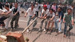 Para mahasiswa merusak pagar kampus mereka untuk bisa keluar dan menggelar unjuk rasa anti-pemerintah pada 14 Mei 1998. Bulan Mei 1998 merupakan momen penting dalam sejarah Indonesia, juga momen penting bagi Soeharto. (KEMAL JUFRI/AFP)