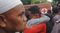 Seorang pria berpelukan sambil menangis setelah gempa bumi di Mamuju, Sulawesi Barat, Indonesia, Jumat (15/1/2021). Gempa ini menyebabkan kerusakan parah pada Hotel Maleo, kantor Gubernur Sulbar, serta RSUD Mamuju. (AP Photo/Azhari Surahman)