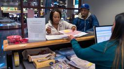 Sepasang calon pengantin Teaira Thompson dan James Anderson menyelesaikan dokumen mereka di Clark County Clerk's di Bandara Internasional McCarran di Las Vegas (12/2). Las Vegas ini menawarkan variasi pernikahan paling banyak. (AFP/L.E. Baskow)