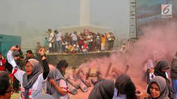Warga bermain serbuk warna-warni saat colour run dalam Festival Damai Millenial Road Safety di Monas, Jakarta, Minggu (23/6/2019). Serbuk warna-warni yang ditembakkan oleh meriam menambah kemeriahan Festival Damai. (merdeka.com/Iqbal Nugroho)