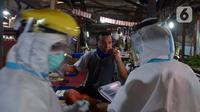 Petugas medis Kecamatan Gambir mendata pedagang saat melakukan tes swab di Pasar Thomas, Jakarta, Rabu (17/6/2020). Tes swab dilakukan untuk memutus rantai penularan virus corona COVID-19. (merdeka.com/Imam Buhori)