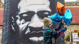 Seorang sukarelawan menghiasi tugu peringatan untuk menandai ulang tahun ke-47 George Floyd di Minneapolis, Minnesota, USA, Rabu (14/10/2020). George Floyd adalah korban perlakuan rasis yang tewas setelah ditindih lutut oleh seorang polisi saat menangkapnya pada 25 Mei 2020. (AFP/Kerem Yucel)