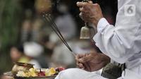 Pemuka agama menyembunyikan lonceng saat memimpin sembahyang Hari Raya Galungan di Pura Aditya Jaya, Rawamangun, Jakarta, Rabu (19/2/2020). Hari Raya Galungan yang merupakan hari kemenangan kebenaran (Dharma) atas kejahatan (Adharma) itu dirayakan setiap 210 hari sekali. (merdeka.com/Iqbal Nugroho)