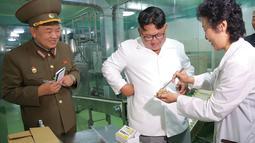 Tawa Pemimpin Korea Utara Kim Jong-un (tengah) saat mengunjungi Pabrik No. 525 di Korea Utara, Rabu (25/7). Pabrik No. 525 memproduksi makanan khusus atau ransum untuk tentara Korea Utara. (STRINGER/AFP/KCNA VIA KNS)