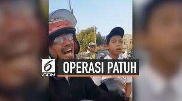 Seorang bapak menangis ketika petugas melakukan razia dalam Operasi Patuh di Makassar, Sulawesi Selatan. Menurut petugas, sang bapak malu karena anaknya tidak mengenakan helm.