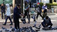 Orang-orang yang memakai masker untuk membantu melindungi dari penyebaran virus corona COVID-19 memberi makan burung merpati di sebuah jalan di Goyang, Korea Selatan, Rabu (11/11/2020). (AP Photo/Ahn Young-joon)