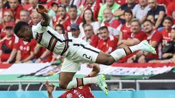 Bek Portugal, Nelson Semedo( atas) saat berebut bola dengan pemain Hungaria, Attila Fiola pada pertandingan grup F Euro 2020 di stadion Ferenc Puskas di Budapest, Hungaria, Selasa (15/6/2021). Portugal menang atas Hungaria 3-0. (Bernadett Szabo/Pool via AP)