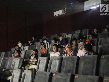 Anak-anak bersiap menyaksikan film di Indiskop atau Bioskop Rakyat di dalam Pasar Jaya Teluk Gong, Penjaringan, Jakarta Utara, Rabu (3/6/2019). Bioskop rakyat ini masih dalam tahap uji coba yang nantinya akan diresmikan pada tanggal 10 Juli 2019 mendatang. (Liputan6.com/Faizal Fanani)