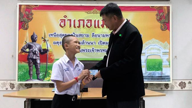 Salah seorang remaja, Mongkol Boonpiam menerima kartu identitas sebagai warga negara Thailand di distrik Mae Sai, Rabu (8/8). Korban gua Thailand tersebut selama ini hidup tanpa memiliki status kewarganegaraan (Chiang Rai Public Relations Office via AP)