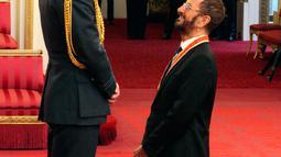 Ringo Starr berbincang dengan Pangeran William setelah menerima gelar kebangsawanan di Istana Buckingham, di London, Inggris (20/3). Ringgo diberi gelar 'Sir' atas jasanya dalam dunia musik. (Yui Mok / PA via AP)