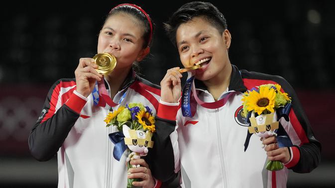 Ganda putri Indonesia Greysia Polii (kiri) dan Apriyani Rahayu saat upacara penyerahan medali cabang badminton ganda putri Olimpiade Tokyo 2020 di Musashino Forest Sport, Senin (2/8/2021). Greysia / Apriyani merebut emas usai menang atas pasangan China Cheng Qingchen/Jia Yi Fan. (AP/Dita Alangkara)