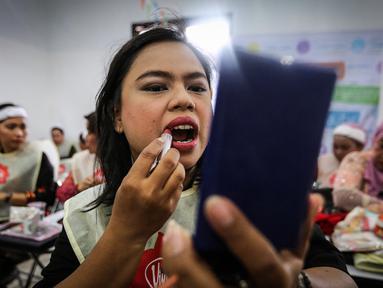 Seorang pengemudi ojek online wanita memoleskan lipstik saat kelas kecantikan jelang peragaan busana di Rawamangun, Jakarta, Jumat (20/4). Kegiatan digelar menyambut Hari Kartini yang jatuh pada 21 April mendatang. (Liputan6.com/Fery Pradolo)