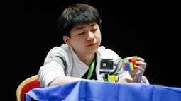 Seorang peserta memerhatikan rubiknya saat mengikuti kejuaraan kubus Rubik Dunia di Saint Denis, Paris, Prancis (16/7). (AFP Photo/Geoffroy Van Der Hasselt)