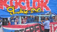 Ketua Panpel Arema, Abdul Haris, melepas spanduk yang dipasang di pagar tribune ketika Arema uji coba melawan Timnas Indonesia U-22 (10/2/2019). (Bola.com/Iwan Setiawan)
