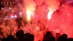 Suporter Galatasaray menyalakan flare saat merayakan kemenangan timnya meraih gelar Liga Turki usai pertandingan melawan Istanbul Basaksehir di Turk Telekom Arena di Istanbul (19/5/2019). Galatasaray memastikan gelar liga Turki ke-22 usai mengalahkan Istanbul Basaksehir 2-1. (AFP Photo/Yasin Akgul)