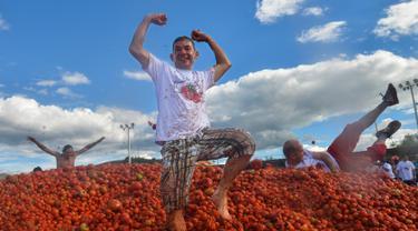 Peserta berdiri di atas gundukan tomat saat Festival Tomatina di Sutamarchan, Boyaca, Kolombia, Minggu (2/6/2019). Perang tomat ini digelar selama tiga hari berturut-turut. (Diana SANCHEZ/AFP)
