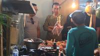 Calon Presiden Nomor Urut 01 Joko Widodo (Jokowi) berdialog dengan pedagang ayam saat blusukan ke Pasar Cihaurgeulis, Bandung, Minggu (11/11). Jokowi berkeliling pasar dan menyapa para penjual juga membeli beberapa bahan pangan (Liputan6.com/Angga Yuniar)
