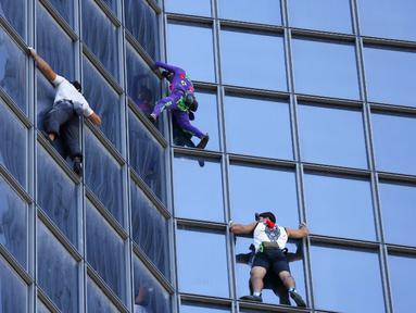 Pendaki Alain Robert (kedua kanan) atau Spiderman Prancis bersama Marcin Banot, Alexis Landot, dan Leo Urban memanjat Menara Total di La Defense, Paris, Prancis, 7 September 2021. Alain dengan tangan kosong memanjat menara setinggi 190 meter itu untuk menentang izin kesehatan. (THOMAS SAMSON/AFP)