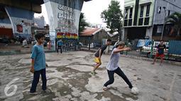 Seorang remaja saat mengiring bola saat bermain di kolong rel kereta kawasan Juanda, Jakarta, Jumat (27/5). Tidak tersedianya ruang terbuka menyebabkan lahan tersebut dijadikan tempat bersosialisasi bagi warga. (Liputan6.com/Immanuel Antonius)