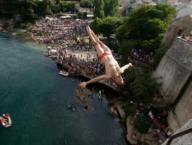 Peserta melompat dari Jembatan Old Mostar pada kompetisi menyelam tradisional ke-452 di Mostar, Bosnia, 29 Juli 2018. Sebanyak 40 penyelam dari Bosnia dan negara tetangga harus melompat dari jembatan setinggi 24 meter ke Sungai Neretva. (AP/Amel Emric)