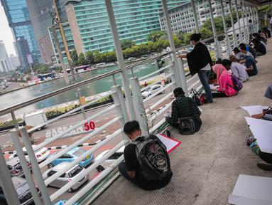 Sejumlah Mahasiswa IKJ Fakultas Seni Rupa melukis suasana Bundaran HI, Jakarta Pusat, Kamis (19/10). Bundaran HI yang telah menjadi ikon kota Jakarta merupakan tempat yang sering dijadikan pusat berbagai aktivitas warga. (Liputan6.com/Faizal Fanani)