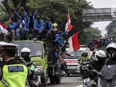 Mahasiswa menaiki truk saat konvoi menuju Gedung DPR/MPR, Jakarta, Kamis (8/10/2020). Mahasiswa ini rencananya akan menggelar aksi menolak UU Cipta Kerja. (Liputan6.com/Johan Tallo)