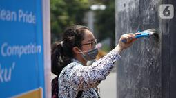 Pelajar membersihkan coretan yang mengotori tembok saat kericuhan dalam unjuk rasa di Senayan, Jakarta, Jumat (4/10/2019). Para siswa dan alumni SMA menutup coret-coretan  itu sekaligus mengampanyekan cinta damai dalam praktik demokrasi di Indonesia. (Liputan6.com/Immanuel Antonius)