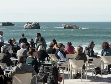Warga dan turis menikmati minuman di sebuah kafe selama cuaca musim dingin yang hangat di sepanjang garis pantai kota Biarritz di Perancis barat (17/2). Kota ini terletak di region Aquitane, Departemen Pyrénées-Atlantiques. (AFP Photo/Iroz Gaizka)