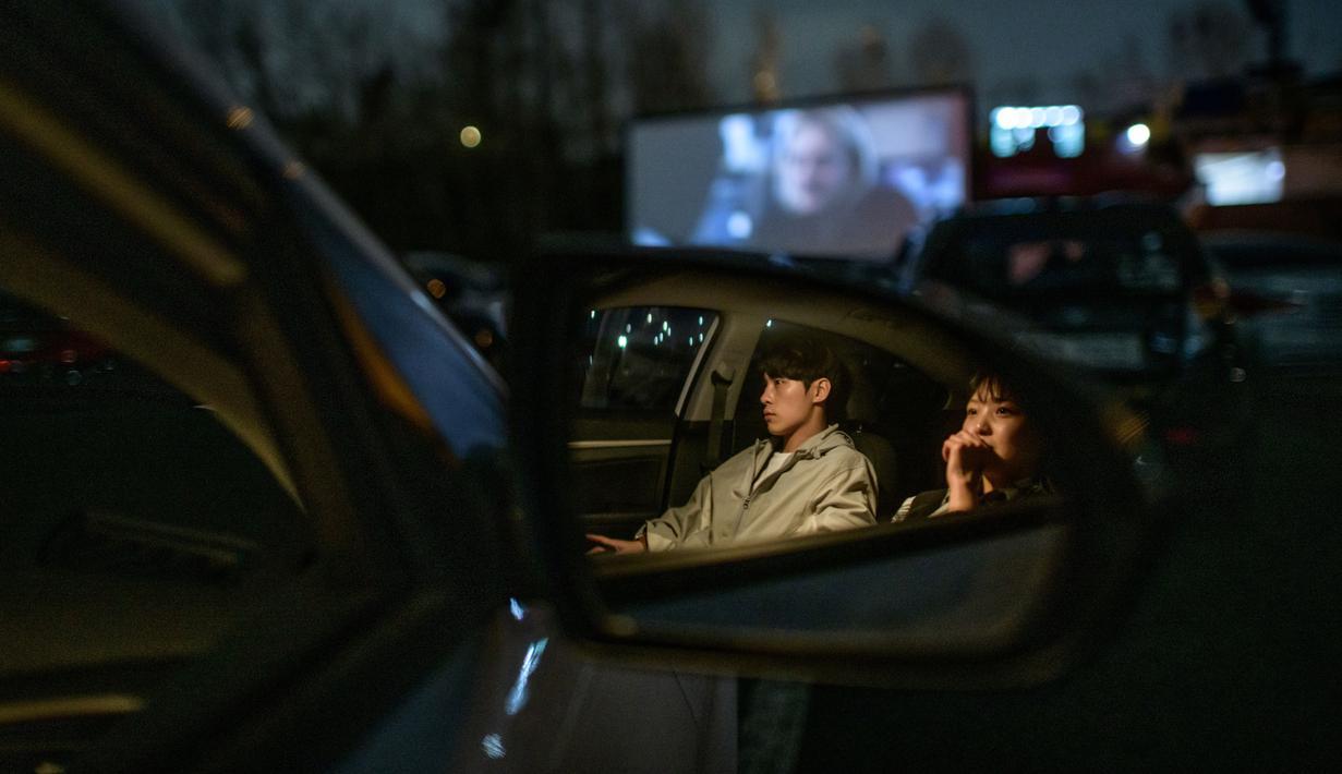 Sepasang suami istri duduk di mobil mereka ketika menonton pemutaran film di sebuah bioskop kendara atau drive-in cinema di Seoul, Korea Selatan, 21 Maret 2020. Jenis bioskop ini menjadi pilihan yang lebih bagi warga Seoul untuk menikmati film di tengah pandemi virus corona Covid-19. (Ed JONES/AFP)