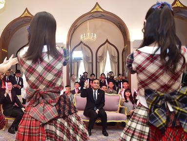 Perdana Menteri Thailand, Prayut Chan-O-Cha menyaksikan grup musik Jepang, AKB48, tampil di Gedung Pemerintahan, Kamis (13/8). Kunjungan ini adalah promosi AKB48 untuk mempersiapkan konser di Bangkok pada Desember mendatang. (HO/ROYAL THAI GOVERNMENT/AFP)