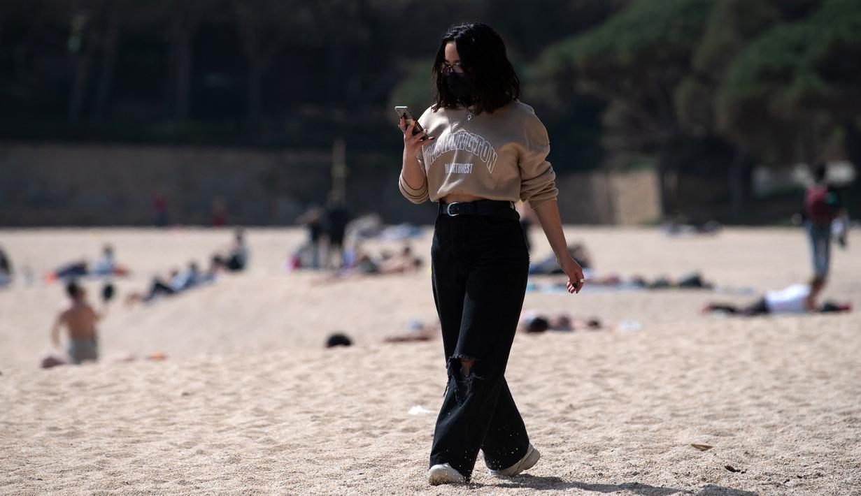 Seorang perempuan yang mengenakan masker berjalan di pantai Sa Conca di Castell-Platja D'Aro dekat Girona, Spanyol pada Rabu (31/3/2021). Spanyol memperketat aturan penggunaan masker dengan mewajibkannya di luar ruangan dan seluruh fasilitas publik. (Josep LAGO / AFP)