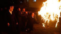 Sekelompok Yahudi ultra ortodoks antizionis menyalakan api unggun di Yerusalem ultra-Ortodoks Mea Shearim, Rabu (2/5). Dalam perayaan Lag BaOmer, ribuan orang Yahudi akan menyalakan api unggun besar. (MENAHEM KAHANA / AFP)