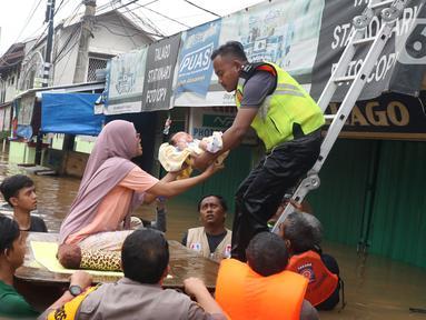 Petugas membantu mengevakuasi bayi yang terjebak banjir di perumahan Ciledug Indah, Tangerang, Rabu (1/1/2020). Banjir setinggi dada orang dewasa terjadi akibat meluapnya kali angke. (Liputan6.com/Angga Yuniar)