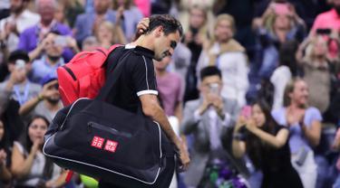 Petenis Roger Federer tertunduk saat berjalan keluar lapangan usai kalah dari Grigor Dimitrov pada perempat final turnamen tenis AS Terbuka 2019 di New York, Amerika Serikat, Selasa (3/9/2019). Dimitrov menang 3-6, 6-4, 6-3, 6-4, 6-2. (AP Photo/Charles Krupa)