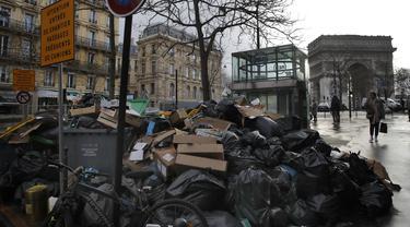 Orang-orang berjalan melewati tumpukan kantong sampah di Paris (4/2/2020). Sampah menumpuk di jalan-jalan Paris dan Marseille karena pemogokan perubahan pada sistem pensiun nasional Prancis.  (AP Photo/Christophe Ena)